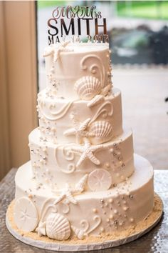 Elegant beach themed white butter cream wedding cake with shells white beach themed wedding cake sea shell wedding cake all white wedding cake junglespirit Image collections