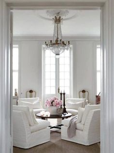 4 comfy armchairs around a low round table with a chandelier overhead