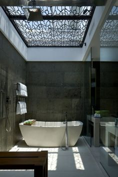 A bathroom featuring a stunning skylight of intricate design that casts varying shadows depending on the light.