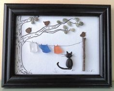 This original framed art picture was created from Lake Michigan beach pebbles, beach glass, a twig and ink on a 5X7 canvas board. It is framed in a recycled black wood frame. The picture features a clothesline tied between a tree and a pole with three birds and a black cat. The framed art work measures 8 1/2 x 6 1/2.