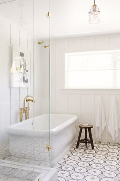 Patterned floor tiles in a bathroom with glass shower and free standing tub