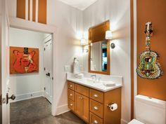Conveniently located next to the stairway, the basement bathroom is full-service, so no one will ever have to leave the party to go upstairs.  Wild guitar art and vibrant orange echo the fun-filled vibe found in the adjacent rec room.