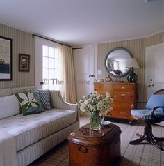 A wooden trunk is used as a coffee table in the seating area of this bedroom which has striped wallpaper and a checked carpet