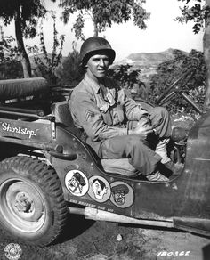 US Army Corporal Paul F. Janesk posing in his jeep in Sicily, Italy, 3 Sep 1943; note cartoon of Axis leaders drawn on his jeep, and Mussolini crossed out (US Army Signal Corps)