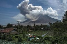 Residents watch as mount Sinabung volcano erupts while travelling by public transport in Karo district, North Sumatra province on May 30, 2015.