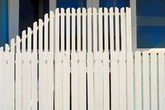 two tiered white picket fence in front of a blue building image by David Smith from Fotolia.com