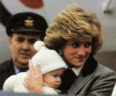March 22, 1985: Princess Diana with baby Prince Harry arriving in Aberdeen, Scotland, with Prince Charles and Prince William (out of view). En route to Balmoral, Scotland. Princess Diana wearing a grey tweed coat, with upper black lapel contrast. She wore this 1983 Scotland too at the airport.