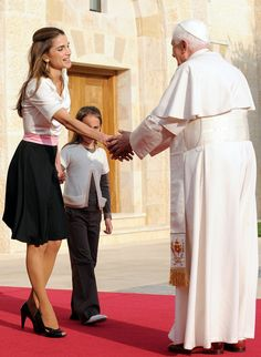 Queen Rania in classic black-and-white knit casuals: short-sleeve white T-shirt and black flare skirt accented with pink waist band