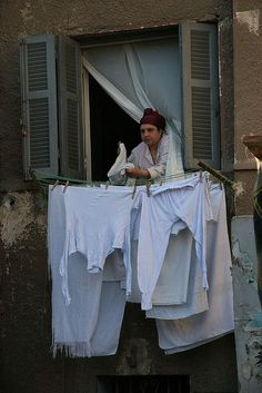 "A woman in the ""City of the Dead"" of Cairo is hanging clothes out of the window // by David Haberlah, via Flickr"
