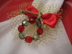 Porta guardanapo com cordão de seda vermelho, contas de acrílico verde e vermelha e fita de cetim vermelha. Obs: Não acompanha o guardanapo. R$ 7,00