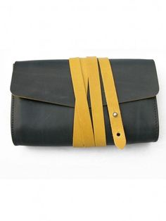M Hulot  Navy garrard clutch£150.00 A clutch bag elegantly criss-crossed with contrast coloured leather strapping and neatly fastened with a single capstun stud. The two-tone effect is pushed further with heavily painted edges matching back to the strap colour.   Interior has zip pocket.   Made in England from veg tan Italian leather   12cm x 20cm x 4.5cm