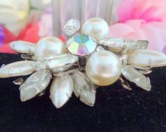 Vintage Judy Lee Silvertone Brooch featuring Lg & Sm Faux Pearls, a Huge Center Rhinestone with Rhinestone Navettes. Signed on the back Judy Lee. See the photos on my store www.CCCsVintageJewelry.com Best, Coco