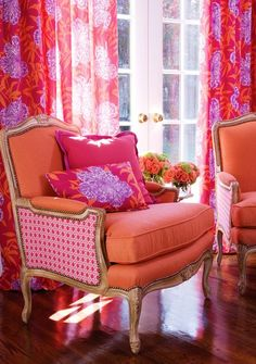 This sitting area is so bright & inviting.  I don't particuarly love the pattern on the chair but the colors, wood floors, pretty vases of roses in the background, oh my!