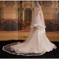 Decadent double tier Cathedral length veil with Aloncon French corded lace scallop.Features of the Venezia veil:-Handmade in Australia.-Includes blusher in a double tier effect.-Can also be also be created in a single tier.-Soft tulle that elegantly frames your gown in Cathedral length.-Alençon French corded lace scallop. Available in a variety of patterns.-Gathered onto metal hair comb that can be moulded and pinned into any hair style.This is a 'made to order' piece and upon ordering will…