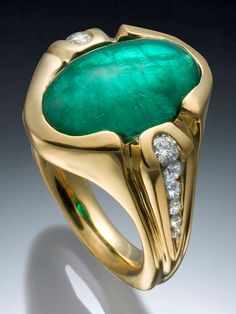 Skylight Jewelers, 18k yellow gold with 5.11ct Emerald oval cabochon, set in a bezel with a tapered channel of diamonds on either side of the shank