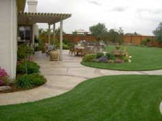 Lovely large back yard created by well done, stained fence, nice landscaping of greens and flowers, curved area separated by stone walkway, a nice seating area, fountain, and a covered area closest to the back of the home.