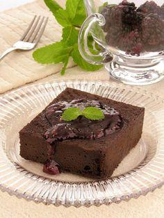 Na foto, um pedaço do bolo de chocolate com calda de framboesa está em um prato de vidro transparente. O bolo tem textura cremosa e a calda escorre pela frente. Ele está decorado com duas folhinhas de hortelã. Ao fundo na decoração está uma taça com framboesas, um ramo de hortelã e um garfo em cima de um guardanapo.
