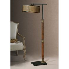 This uniquely beautiful floor lamp has a rustic appearance with its distressed, burnished wood and aged black details. The round drum shade complements the base with a golden bronze color and aged black metal trim.