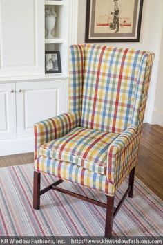 A favored shaker wing-back chair is smartly upholstered in a traditional check pattern that matches the drapes and furnishings throughout the home.  The repeat pattern of the stripe matches exactly to the seat cushion, just as the pattern on the custom upholstered arms and wings match on either side. Room designed by F.D. Hodge Interiors
