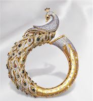 Handcrafted yellow gold kada adorned with diamonds,rubies and sapphires.