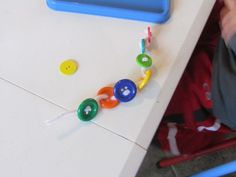 I explained to the children that they could thread the pipe cleaners through the holes of the buttons to make a bracelet. I showed them two methods of threading. The first method was to push the pipe cleaner up through one hole and back down through another hole then slide the button over – which is very hard to do.