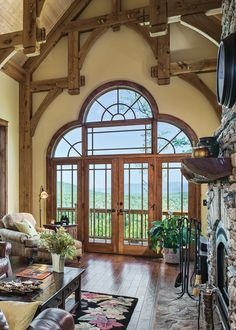 Elegant hammer beam trusses frame a vast vista from this casual great room. Meticulous attention to detail was taken in every aspect of the woodwork, from the dark hardwood floors to the ceiling's blond tongue-and-groove. A soft buttercup yellow shade on the walls pulls the whole space together.