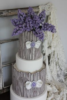 Shabby Chic and lilac inspired cake designed and created by Veronica Arthur for Cake Central Magazine. For this design I created a new technique which replicates old weathered wood with peeling paint. It is entirely edible!  The old weathered window prop is from an old South Carolina farm house built in 1914. The tattered lace table cloth belonged to my husband's great grandmother.  Photos and styling by Veronica Arthur. ~With Love & Confection