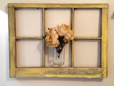 Old rustic window frame lightly painted yellow with a mason jar flower vase.