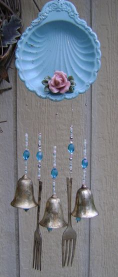 wind chime i made from old metal candy tray. spray painted, drilled holes for wires and hanging. glued a broken china rose on it.