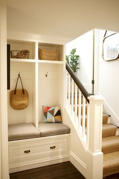 A staircase lined with beadboard trim leads to a basement mudroom boasting built-in lockers with a bench and drawers
