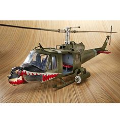 "UH-1 Huey B ""Shark Mouth"" Model    model has been replicated after those used in Vietnam with simulated war damage and is equipped with 40mm gun nose and 2 x 7 rocket pods. The side bay doors do open to a detailed inside interior. Painted on the front ""Shark Mouth,"" which was adopted after the P-40 Flying Tigers. Both main and tail rotors rotate with a slight push. Model measures about 31""l with a main rotor span of 27""w. 1/18 scale of the actual UH-1 Huey size."