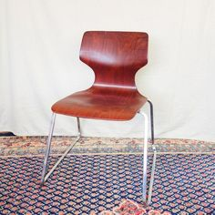 A mid century modern composite wood and chrome Flototto chair by Pagholz, West Germany. It has a beautiful sleek, streamlined design that will work in many settings from an occasional chair to a desk chair.The chair is made from Pagwood, a high density wood veneer composite. The Pagwood material is scratch, and stain resistant. The chair has a shaped seat and a waisted back. It is supported by a square chrome frame. It is marked Pagholz Pagwood, Industrial Chair, Industrial House, Stack Of Books, Occasional Chairs, Desk Chair, Home Staging, Wood Veneer, Vintage Home Decor, Modern Chairs