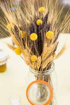 A dried floral arrangement featuring wheat, lavender, and yellow billy balls | WedAZ.com | Wedding Articles