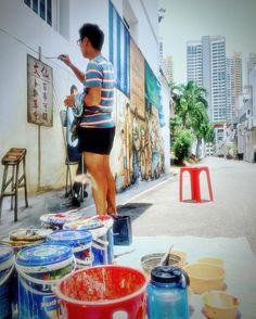 In the streets of #TiongBahru found a local artist painting the walls with a traditional image of the old neighborhood. #Singapore #streetart #exploresingapore