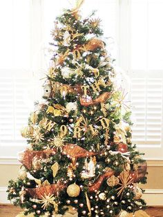 "Get the metallic look by adding nothing but gold to your Christmas tree. Start by creating a foundation with gold ball ornaments, then fill in with gold starbursts, gilded ""Joy to the World"" garland, and figurines. For added effect, first lay all the ornaments on a drop cloth and spray with a layer of glitter paint. Let dry before hanging. (image credit: Mallory Fitzsimmons)"