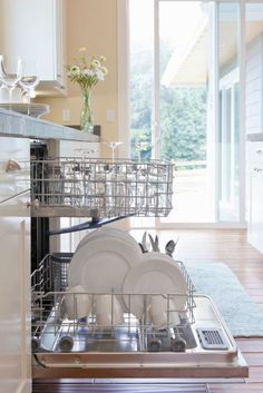 """Without a proper monthly cleanse, your """"self-cleaning"""" dishwasher can become a cesspool of bacteria, fungi, black yeast, and even mold. Not to mention it can also emit a foul odor, thanks to leftover food particles. To kill germs, erase soap scum and cut through films of grease. Start by picking up debris from the bottom of the drain with a rag or paper towel. """"Then, pour white vinegar into a cup, place it on the top rack of an empty dishwasher, and run a full cycle on the hottest water…"""