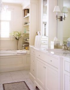 Love this white bathroom; marble counters, white inset cabinets, crystal knobs, sconces in mirror, mirrored uppers resting on lowers, windows over bathtub