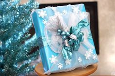 """Fans of *Frozen* will love this beautiful gift-wrap idea inspired by the hit animated movie. With glittery blue accents, shimmering organza and a cascade of snowflakes, it looks like Elsa's dress has taken on new life as a present under your tree. You may not be able to """"let it go."""""""