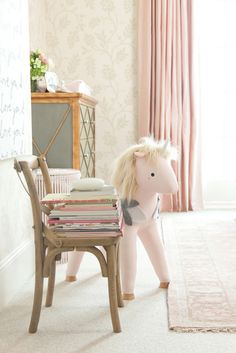 Cute details in this pink and gold nursery // pink rocking horse, stacked books on miniature chair