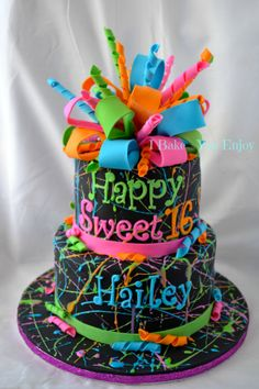 "- Splatter Paint Cake * I love the splattering of ""paint"" (royal icing) onthe black canvas! Topped with a colorful poofy bow made of gum paste."
