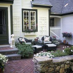 like the brick patio with chairs near house with planter under window.  Hmmm...backyard under kitchen window??
