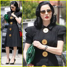 Dita in a simple black dress with oversized buttons