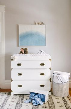 Chic boy's nursery boasts a blue abstract art piece lining gray walls over a white campaign dresser, Land of Nod Campaign Dresser, topped with a changing pad atop a Beni Ourain Rug.