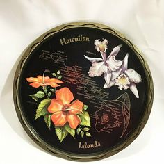Hawaiian Island Round Vintage Tray Metal 11 Orchid Hibiscus Hawaii Souvenir Slight water ring on the front by the word Orchid Dent on one edge of the round tray 10 inches in diam