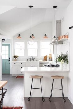 white minimalist kitchen with rustic industrial bar stools and hanging pendant lights