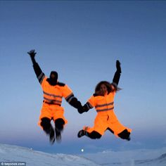 Jumping for joy: Another image sees the couple holding hands as they leap into the air while situated in a white snowy winter wonderland