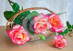 Wicker basket with a beautiful bright roses on the table surface.
