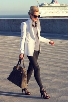 White peacoat, light grey sweater, statement necklace, black leather look jeans, oversized bag and strappy pumps