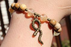 What you see is what you get - this is the only one of this bracelet I will make! Get it before its gone! - Picture Jasper round beads - Tourmaline round beads - Antiquated bronze tone spacer beads - Antiquated bronze tone snake charm - 7 inches un-stretched (approximately). This bracelet best fits people with a medium frame. - Ships from Canada.  A charming bracelet for you, a friend, or a friendly snake charmer! Take this with you traveling to ward off any unwanted slithery friends!  All…