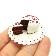 This miniature polymer clay dollhouse cake is a chocolate cake with red frosting in the middle and white frosting on top. There are also miniature red hearts and sprinkles on top. It's hand sculpted o